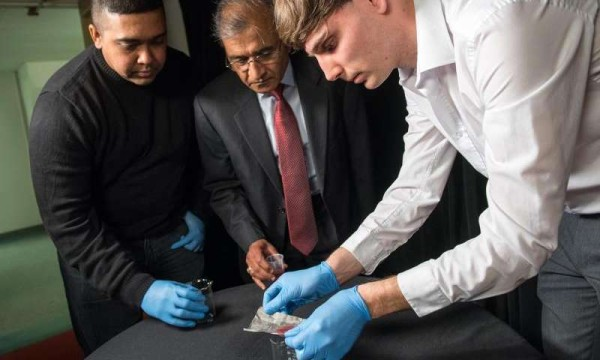 Bharat Bhushan (Ohio Eminent Scholar in Mechanical Systems, center), research assistant Dave Maharaj (left) and postdoctoral researcher Philip Brown (right) -- all of The Ohio State University -- demonstrate new technology they have developed for separating oil from water. Credit: Jo McCulty, courtesy of The Ohio State University.